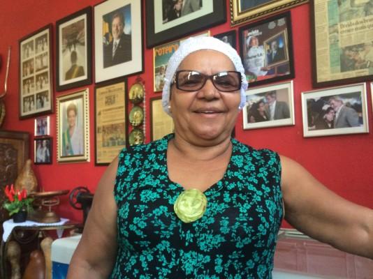 Bakom Tia Zélia hänger de signerade porträtten av Dilma och Lula.