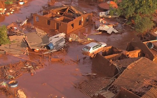 Lermassorna täcker en av byarna längs floden med  det giftiga avfallet från järnmalmsgruvan.