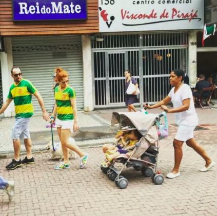 Ett par går till anti-Dilmademonstrationen i Rio medan sin hemhjälp i vit uniform.
