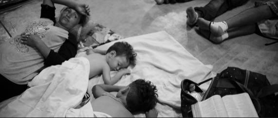 34-åriga Rosa Dubon och hennes två söner vilar ut på golvet till en idrottshall.